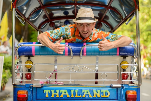 Portrait of young handsome man riding tuk tuk comme transport public local dans la ville de bangkok