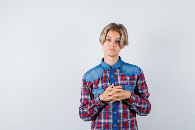 Portrait of young teen boy gardant les doigts entrelacés en chemise à carreaux et à la vue de face pensive