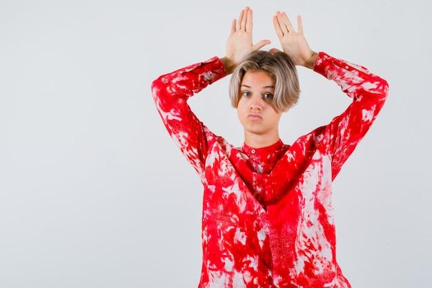 Portrait of young teen boy gardant les mains sur la tête comme les oreilles en chemise et à la vue de face perplexe