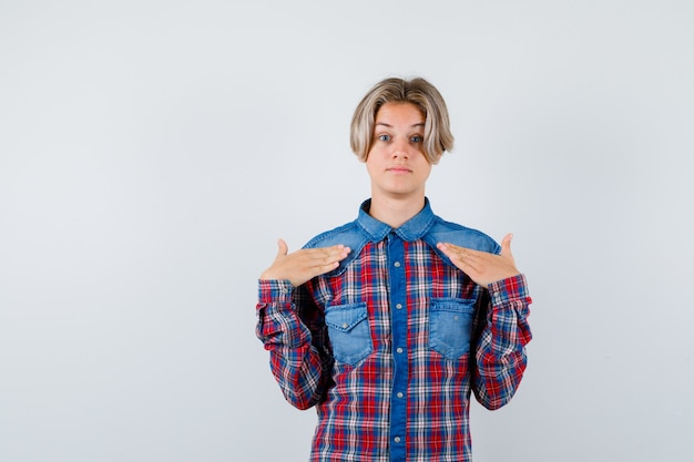 Portrait of young teen boy pointant sur lui-même en chemise à carreaux et à la vue de face perplexe