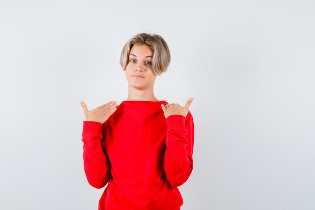 Portrait of young teen boy pointant sur lui-même en pull rouge et à la fière vue de face