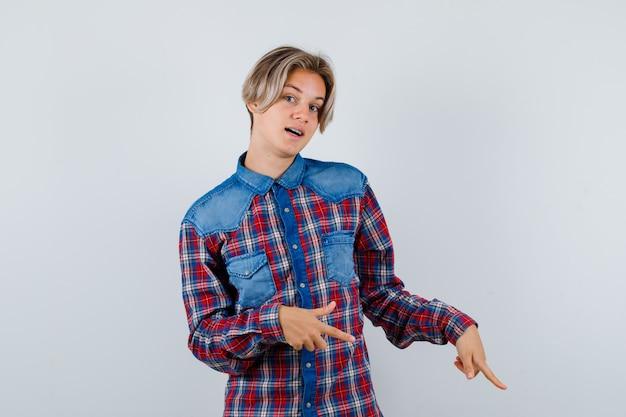 Portrait of young teen boy pointant vers le bas en chemise à carreaux et à la curieuse vue de face