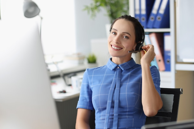 Portrait d'une opératrice souriante dans les écouteurs sur le lieu de travail