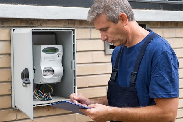 Portrait d'ouvrier électricien inspectant le compteur électrique