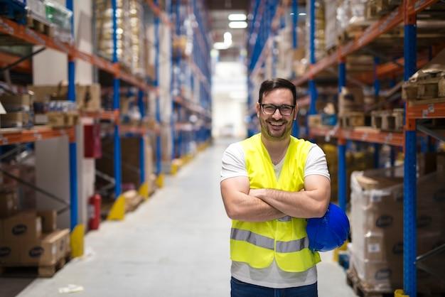 Portrait d'ouvrier d'entrepôt d'âge moyen debout dans un grand centre de distribution d'entrepôt avec les bras croisés