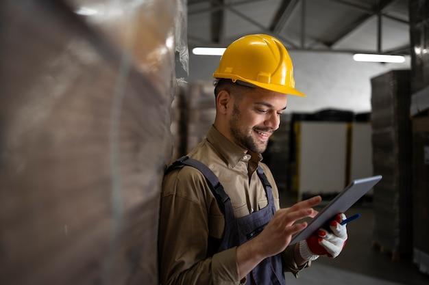 Portrait d'ouvrier d'entrepôt souriant caucasien debout par palettes et vérification de l'inventaire sur ordinateur tablette dans la salle de stockage.