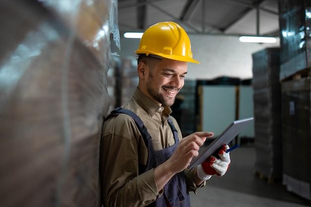 Portrait d'ouvrier d'entrepôt souriant caucasien debout par palettes et vérification de l'inventaire sur tablette en entrepôt.
