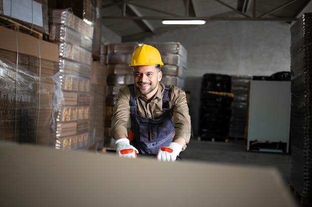 Portrait d'ouvrier d'entrepôt souriant caucasien poussant la charge et les palettes sur chariot élévateur manuel dans la salle de stockage.