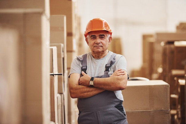 Portrait d'un ouvrier de stockage senior dans un entrepôt en uniforme et casque.