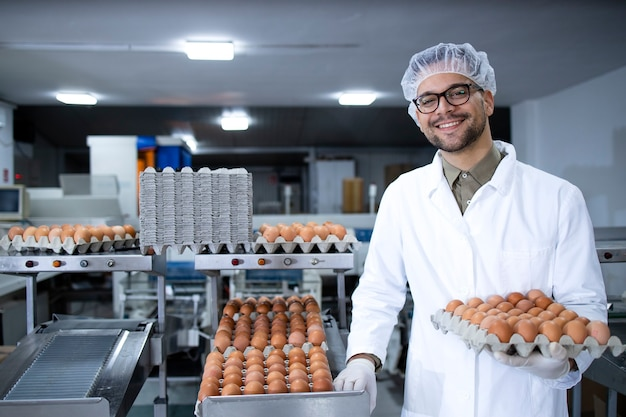 Portrait d'ouvrier d'usine alimentaire avec filet à cheveux et gants hygiéniques tenant des œufs par transport industriel et machine d'emballage dans une usine de transformation des aliments.