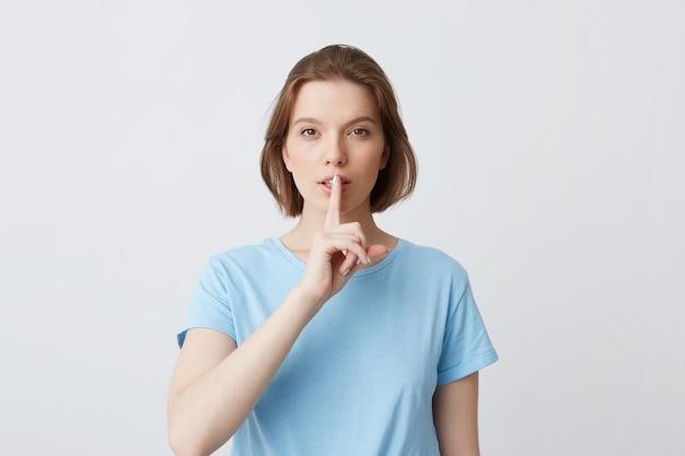 Portrait de paisible belle jeune femme en t-shirt bleu regarde directement à huis clos et montrant le geste de silence