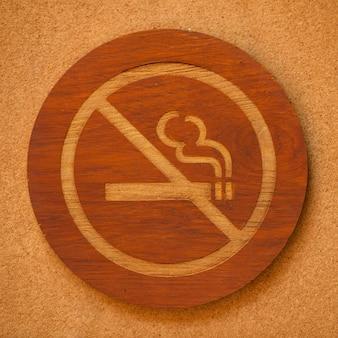 Portrait de panneau en bois non fumeur contre mur marron