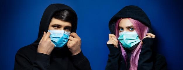 Portrait panoramique studio sombre de jeune couple à capuchon, gars et fille portant un masque médical contre le coronavirus, sur fond de couleur bleu fantôme.