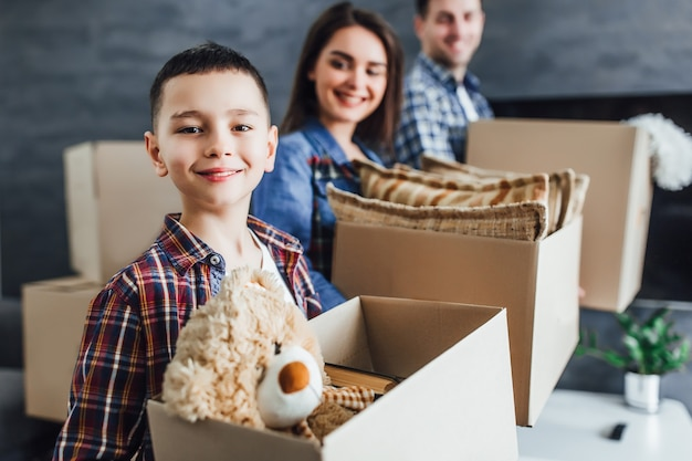 Portrait d'un parent et d'un enfant avec une boîte en carton, déménageant dans une nouvelle maison