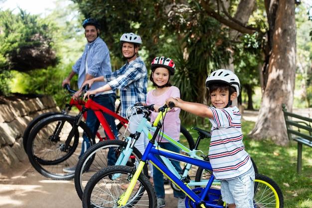 Portrait des parents et des enfants debout à vélo dans le parc
