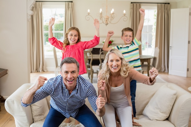 Portrait de parents et d'enfants s'amusant dans le salon