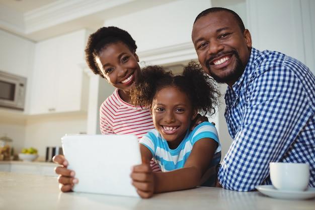Portrait, parents, fille, utilisation, tablette numérique, cuisine