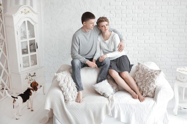 Portrait de parents heureux avec leur fille et leur animal de compagnie bien-aimé avec un salon