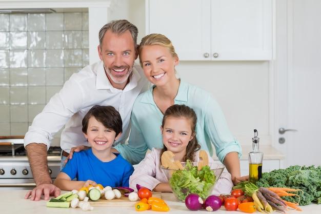 Portrait des parents et de leurs deux enfants debout dans la cuisine