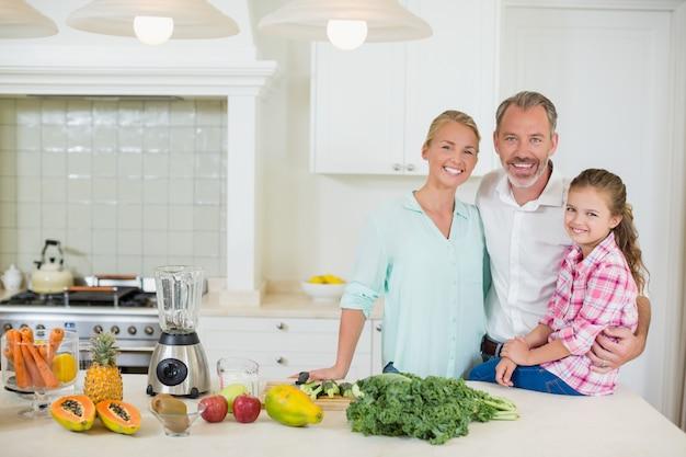 Portrait de parents avec sa fille dans la cuisine