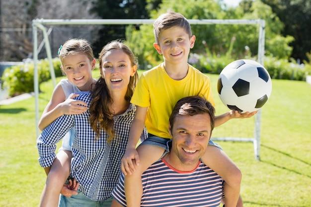 Portrait de parents souriants portant leurs deux enfants sur leurs épaules