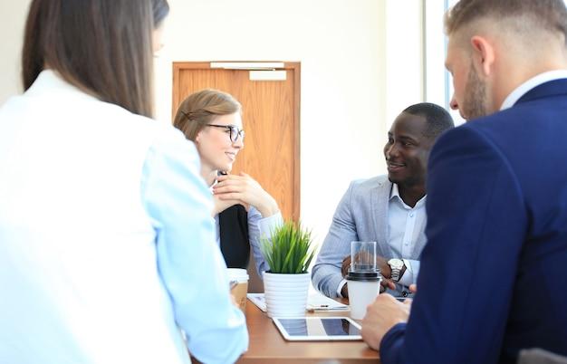 Portrait de partenaires commerciaux intelligents planifiant le travail lors d'une réunion
