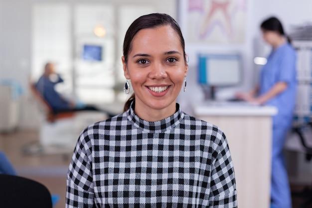 Portrait d'une patiente souriante regardant la caméra assise sur une chaise dans la salle d'attente de la clinique stomatologique