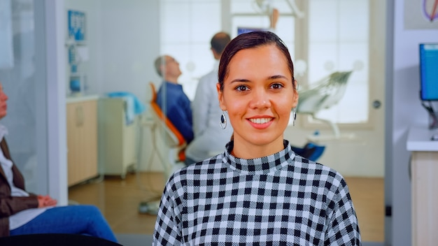 Portrait d'une patiente souriante regardant une webcam assise sur une chaise dans la salle d'attente de la clinique stomatologique. assistant stomatologue tapant sur pc dans un cabinet dentaire pendant que le médecin travaille en arrière-plan.
