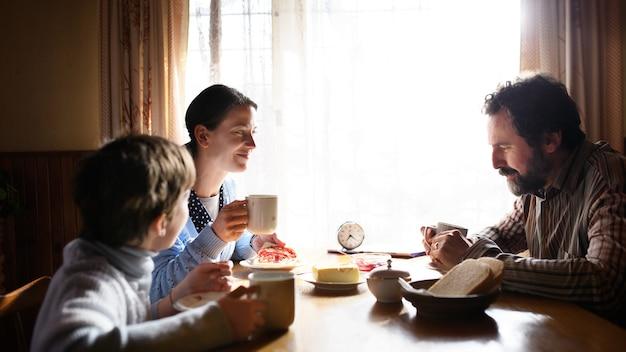 Un portrait d'une pauvre petite fille triste avec des parents mangeant à l'intérieur à la maison, concept de pauvreté.