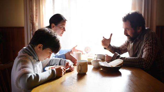 Portrait d'une pauvre petite fille triste avec des parents mangeant à l'intérieur à la maison, concept de pauvreté.