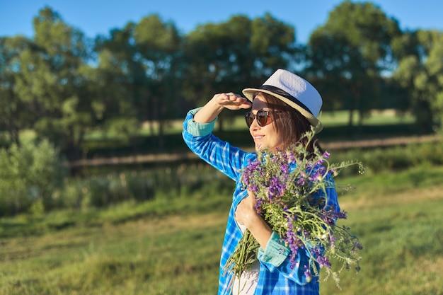 Portrait De Pays D'une Belle Femme Adulte Au Chapeau Avec Bouquet De Fleurs Sauvages. Paysage Naturel Vert, Prairies D'été De Printemps, Femme Regarde Au Loin, Espace De Copie Photo Premium