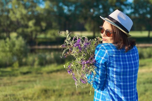 Portrait de pays d'une belle femme adulte au chapeau avec bouquet de fleurs sauvages. paysage naturel vert, prairies d'été de printemps, femme regarde au loin, espace de copie