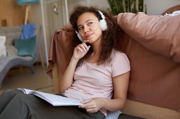 Portrait de pensée jeune fille mulâtre bouclée dans la chambre, vêtue d'un pyjama, appréciant sa chanson préférée et lisant un nouveau magazine sur l'art, détourne les yeux rêveurs.
