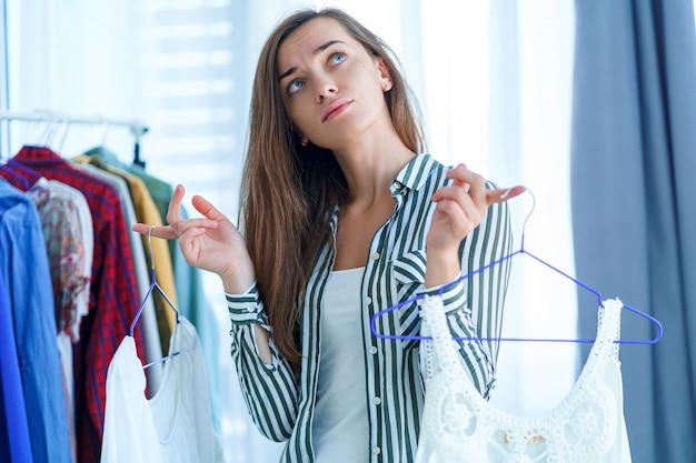 Portrait de la pensée a souligné la jeune femme brune lors du choix de la tenue lors de l'achat de vêtements féminins à la boutique de tissus