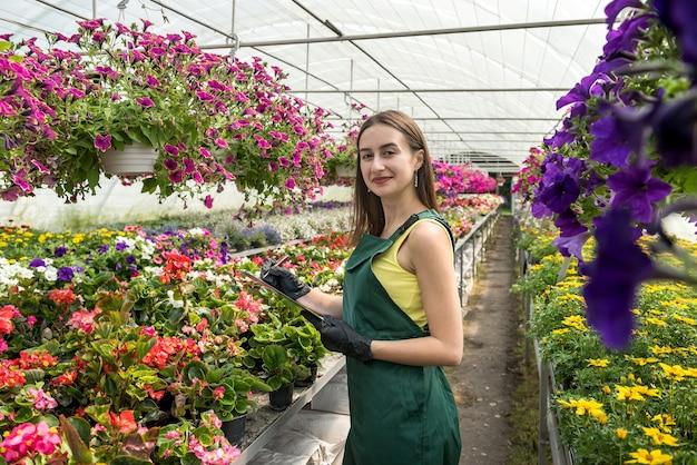 Portrait de pépinière féminine au travail en serre, tenant le presse-papiers et vérifie l'état des plantes. printemps