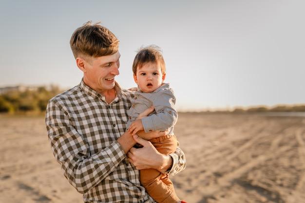 Portrait de père aimant et son fils d'un an marchant et jouant à l'extérieur.
