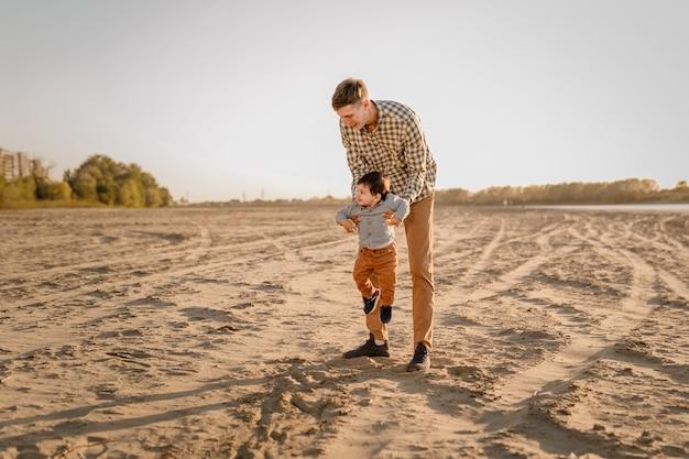Portrait d'un père aimant et de son fils d'un an marchant et jouant à l'extérieur.