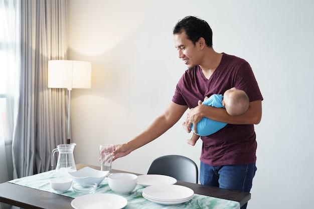 Portrait de père célibataire faisant des corvées à la maison tout en portant son bébé