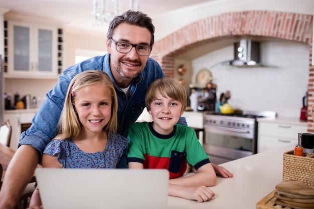 Portrait, père, enfants, ordinateur portable, cuisine