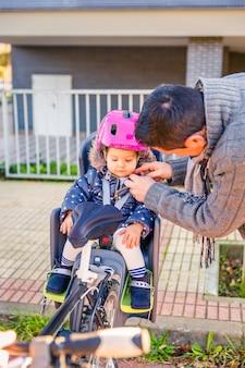 Portrait de père fermant le casque de sécurité de vélo à sa petite fille assise dans le siège de vélo. concept de sécurité et de protection des enfants.