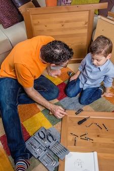 Portrait de père et fils assemblant avec des outils un nouveau mobilier pour la maison. concept de loisirs en famille