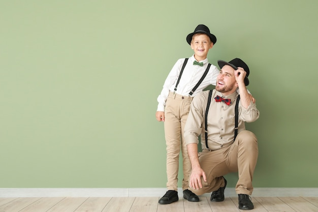 Portrait de père et fils à la mode près du mur de couleur