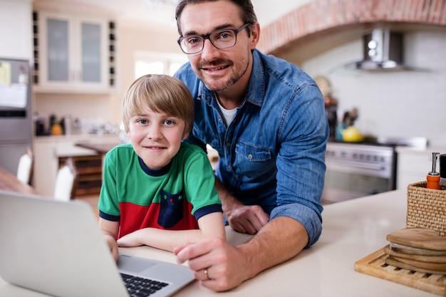 Portrait, père, fils, ordinateur portable, cuisine