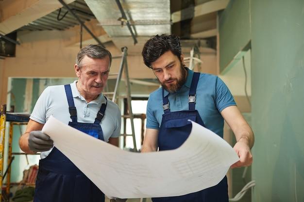 Portrait de père et fils regardant les plans d'étage lors de la rénovation de la maison ensemble, copiez l'espace