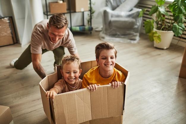 Portrait d'un père heureux jouant avec deux fils dans une boîte en carton pendant que la famille déménage dans un nouveau policier de maison...