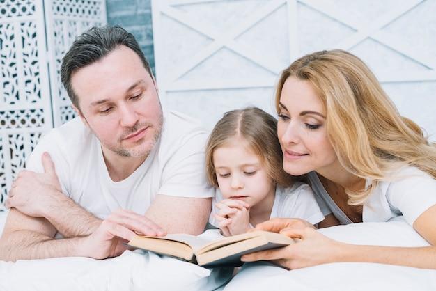 Portrait de père; livre de lecture de mère et fille sur le lit