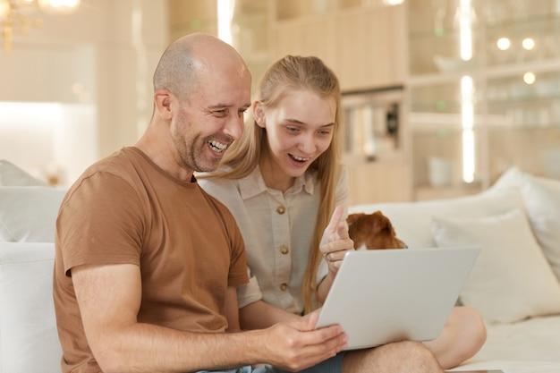 Portrait de père mature souriant joyeusement tout en regardant l'écran du portable avec une adolescente alors qu'il était assis sur le canapé à l'intérieur de la maison