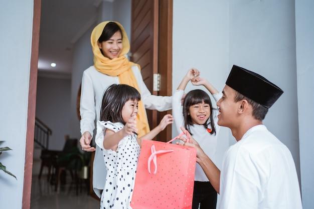 Portrait de père musulman donnant un cadeau à ses enfants sur eid mubarak