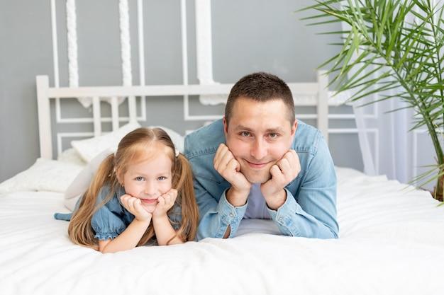 Portrait d'un père avec une petite fille s'amusant sur le lit à la maison