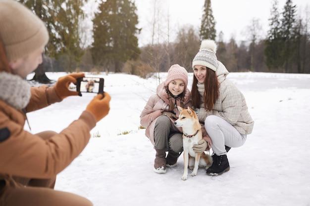 Portrait d'un père prenant une photo d'une fille et d'une femme mignonnes avec un chien tout en profitant d'une promenade à l'extérieur dans la forêt d'hiver, espace pour copie